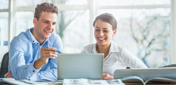 Index Solutions couple talking in front of monitor